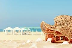 Cappello femminile di modo della spiaggia sopra la valigia della paglia nella sabbia Concetto tropicale di vacanze estive fotografia stock