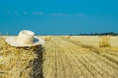 Cappello funzionante di un agricoltore su un mucchio di fieno Comcept di agricoltura Concetto della raccolta Fotografia Stock