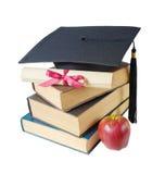 Cappello, libri, mela e rotolo laureati Fotografie Stock