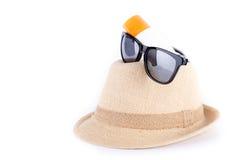 Cappello, occhiali da sole, lozione del corpo isolata su bianco Fotografie Stock Libere da Diritti