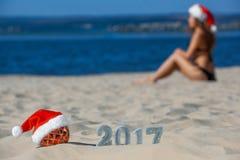 Cappello rosso di Santa Claus che dura sulla palla di Natale che si trova sulla spiaggia, accanto alla sabbia del nuovo anno con  Immagini Stock