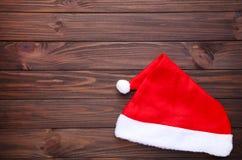 Cappello rosso di Santa Claus su fondo di legno marrone immagini stock