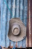 Cappello tropicale che appende su una parete dello zinco della ruggine in un'azienda agricola della capanna in Asia Fotografie Stock Libere da Diritti