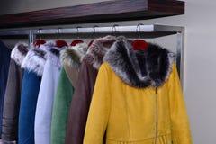 Cappotti assortiti che appendono sullo scaffale del negozio immagine stock