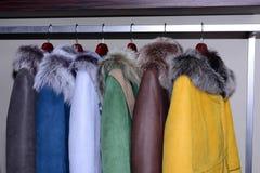 Cappotti assortiti che appendono sullo scaffale del negozio fotografie stock libere da diritti