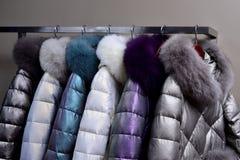Cappotti caldi con i collari della pelliccia che appendono sullo scaffale fotografie stock libere da diritti