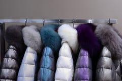 Cappotti caldi con i collari della pelliccia che appendono sullo scaffale fotografie stock