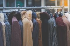 Cappotti di inverno appesi su uno scaffale dei vestiti Fotografia Stock Libera da Diritti