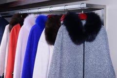 Cappotti eleganti che appendono sullo scaffale fotografie stock libere da diritti