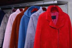 Cappotti molli che appendono sulla ferrovia in negozio immagini stock libere da diritti