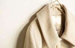 Cappotto beige della lana che appende sulla gruccia per vestiti su fondo bianco fotografia stock