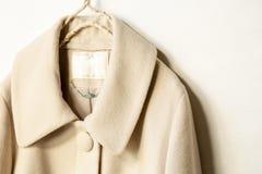 Cappotto beige della lana che appende sulla gruccia per vestiti su fondo bianco fotografie stock