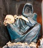 Cappotto con il cranio umano sul ginocchio Fotografie Stock Libere da Diritti