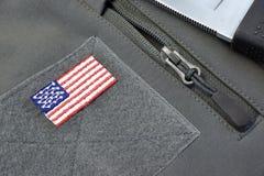 Cappotto con la toppa della bandiera americana, la chiusura lampo d'argento ed il coltello di battaglia fotografia stock