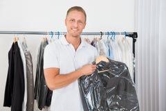 Cappotto della tenuta dell'uomo nel deposito di lavaggio a secco immagini stock libere da diritti