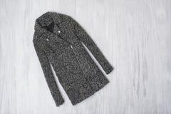 Cappotto di lana grigio su fondo di legno concetto alla moda immagini stock libere da diritti