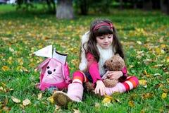 Cappotto di pelliccia da portare della bambina sveglia nella foresta di autunno Immagini Stock