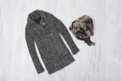 Cappotto e skarf di lana grigi su fondo di legno Raggiro alla moda immagine stock libera da diritti