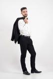 Cappotto elegante dello smoking della tenuta dell'uomo sopra la sua spalla che esamina macchina fotografica fotografia stock libera da diritti