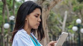 Cappotto femminile del laboratorio del dottore Reading Tablet Wearing fotografia stock libera da diritti