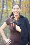 Cappotto teenager di risata della tenuta della ragazza sulla spalla Fotografia Stock