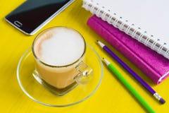 Cappucс ino, notaboeken en een telefoon op een lijst Stock Fotografie