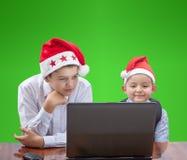 In cappucci dei bambini di Santa Claus con interesse stanno esaminando un computer portatile Fotografia Stock Libera da Diritti