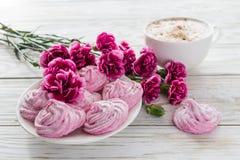 Cappuccino και σπιτικό marshmallow επιδόρπιο, ρόδινα γαρίφαλα στον ξύλινο πίνακα Στοκ Φωτογραφία