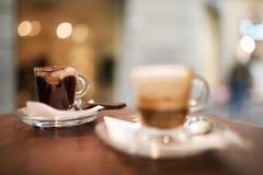 Cappuccino και espresso που εξυπηρετούνται σε έναν πίνακα bistro Στοκ Φωτογραφίες