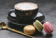 Cappuccino με marshmallow στο μαύρο φλυτζάνι, macaroons, κουτάλι στο σκοτεινό υπόβαθρο Στοκ εικόνα με δικαίωμα ελεύθερης χρήσης