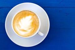Cappuccino στο άσπρο κεραμικό φλυτζάνι με το πιατάκι στο μπλε χρωματισμένο ξύλο Στοκ Φωτογραφίες