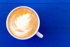 Cappuccino στο άσπρο κεραμικό φλυτζάνι στο μπλε χρωματισμένο ξύλο άνωθεν Στοκ εικόνες με δικαίωμα ελεύθερης χρήσης