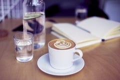 Cappuccino φλιτζανιών του καφέ, ποτήρι του καθαρού νερού, μπουκάλι στον ξύλινο πίνακα, φωτεινό εσωτερικό φως της ημέρας Στοκ φωτογραφία με δικαίωμα ελεύθερης χρήσης