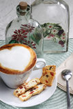 Cappuccino. Cup with sweet delicious cookies on a table set. Heart shape coffee foam Royalty Free Stock Photography