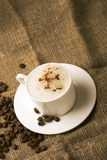 Cappuccino. Cup of cappuccino at the sacking with whole grains of coffee Royalty Free Stock Photo