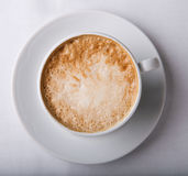 Cappuccino. In white cup and a plate Royalty Free Stock Image