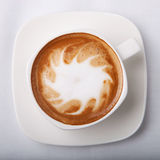 Cappuccino. In white cup and a plate Royalty Free Stock Images