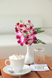 Cappuccino. And orchid flower in a contemporary bistro Royalty Free Stock Image