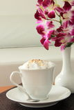 Cappuccino. And orchid flower in a contemporary bistro Stock Photography