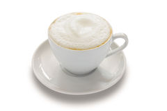 Cappuccino. With a frothy white top in a white ceramic cup over a white background Royalty Free Stock Image