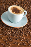 Cappuccino. With chocolate sprinkles on coffee beans Royalty Free Stock Photography