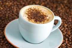 Cappuccino. With chocolate sprinkles on coffee beans royalty free stock photo
