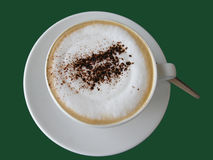 Cappuccino. Top view on a big cup of fresh Italian Cappuccino with cacao decoration isolated on green studio background Royalty Free Stock Photo