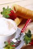 Cappuccino and afternoon snack. Cappuccino with strawberries and afternoon snack on wood of fir Stock Images