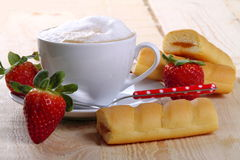 Cappuccino and afternoon snack. Cappuccino with strawberries and afternoon snack on wood of fir Stock Photos