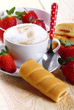 Cappuccino and afternoon snack. Cappuccino with strawberries and afternoon snack on wood of fir Stock Photo