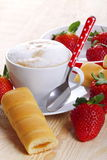 Cappuccino and afternoon snack. Cappuccino with strawberries and afternoon snack on wood of fir Royalty Free Stock Photography
