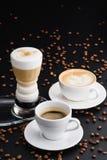 Cappuccino, Americano et latte en une photo sur un fond noir Photographie stock libre de droits