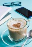 Cappuccino, Anmerkungsbücher und ein Telefon auf einer Tabelle Lizenzfreies Stockfoto