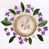 Cappuccino with aroma cinnamon and lilac. Flat lay frothy coffee with cinnamon garnished with flowers of lilac top view Stock Image